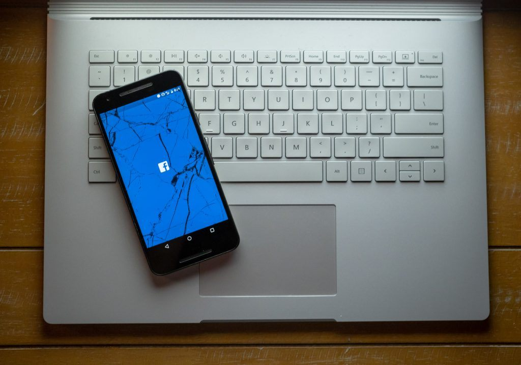 Facebook app on a smartphone with a cracked screen